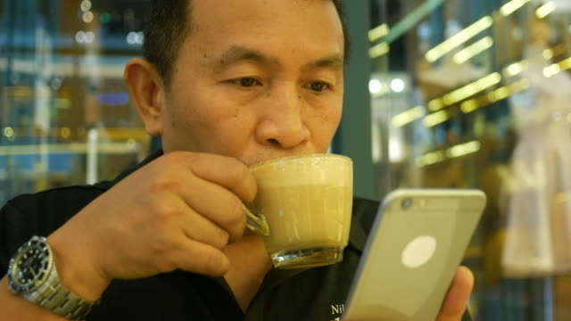 mature man using phone in coffee shop - mourner stock videos and b-roll footage