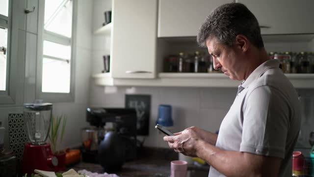 vídeos de stock, filmes e b-roll de homem maduro usando smartphone em casa - conveniência