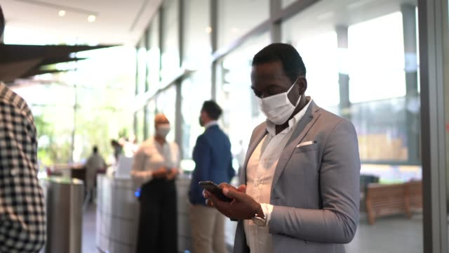 mature man waiting elevator using mobile phone on office's lobby - with face mask - business people in a row stock videos & royalty-free footage