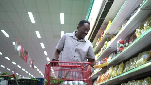 mature man walking and using mobile in supermarket - manufactured object stock videos & royalty-free footage