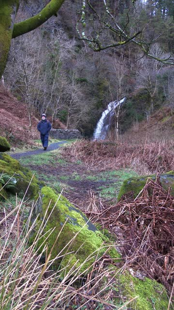 mature man walking away from a waterfall - johnfscott stock videos & royalty-free footage