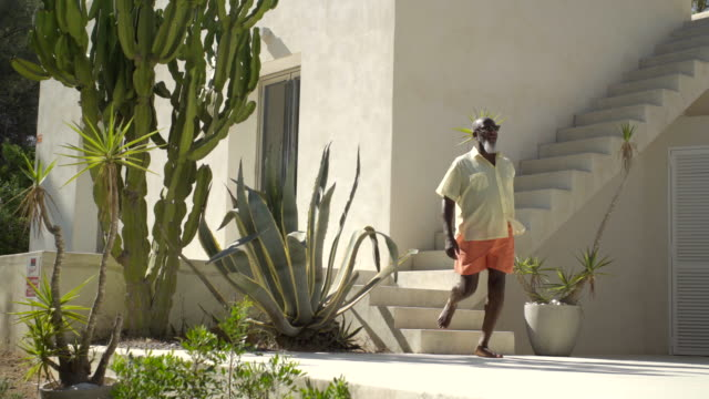mature man walks through luxury villa - terrasse grundstück stock-videos und b-roll-filmmaterial