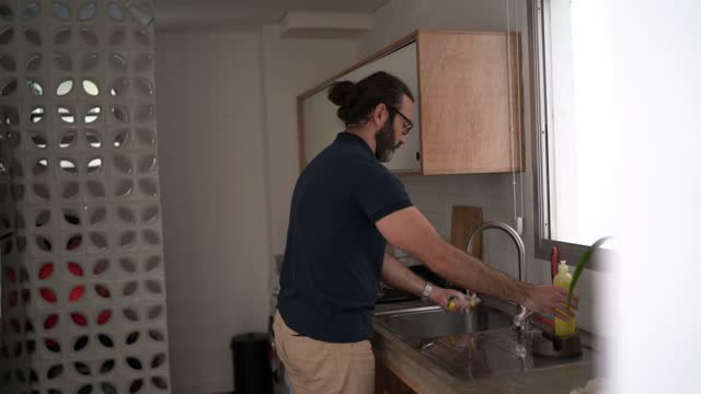 mature man washing dishes at home - genderblend stock videos & royalty-free footage