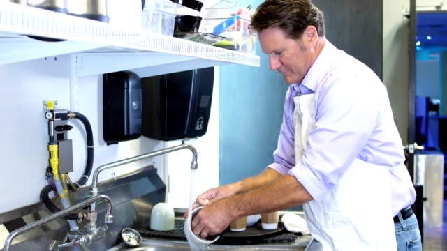 成熟的男人洗碗在咖啡店水槽 - 僅一成熟男士 個影片檔及 b 捲影像