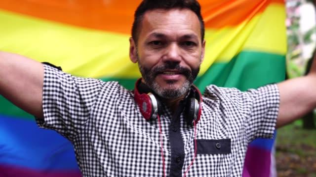 mature man waving rainbow flag - rainbow flag stock videos and b-roll footage