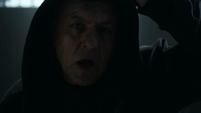 uomo maturo che indossa la felpa con cappuccio in palestra - giacca video stock e b–roll