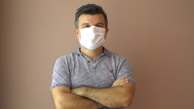mature man wearing surgical mask for prevention. - brown background stock videos & royalty-free footage