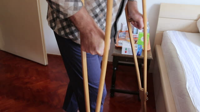 mature man with crutches going to bed while female nurse assisting him - crutch stock videos & royalty-free footage
