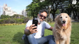 Mature man with golden retriever dog walking in the park in afternoon