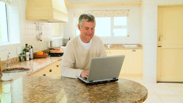 Mature man with laptop in kitchen / Cape Town, Western Cape, South Africa