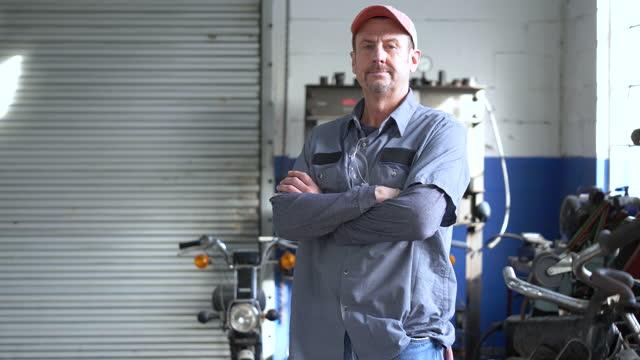 reifer mann, der als automechaniker in der werkstatt arbeitet - ernst stock-videos und b-roll-filmmaterial