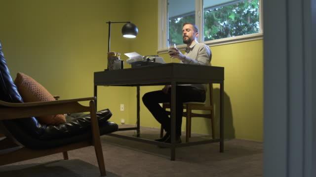 mature man working from home in office, using typewriter. - 書斎点の映像素材/bロール