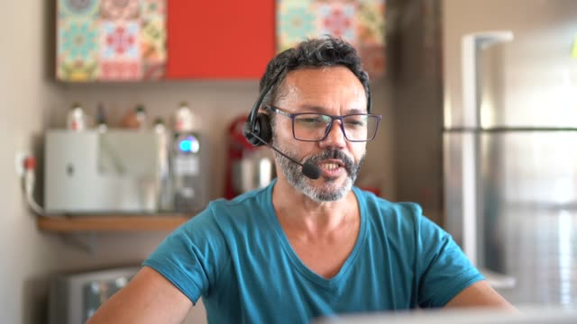 mature man working from home, using headset during video call or customer call - call centre stock videos & royalty-free footage