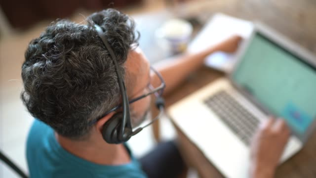 mature man working from home, using headset during video call or customer call - laptop remote location stock videos & royalty-free footage