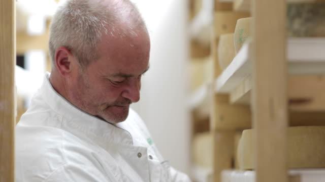 vidéos et rushes de homme mûr travaillant dans la salle de stockage de séchage de fromage - cheese