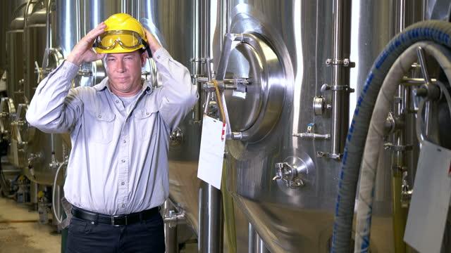 vídeos de stock e filmes b-roll de mature man working in factory putting on hardhat - 40 44 anos