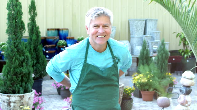 a mature man working in plant nursery, puts on apron - only mature men stock videos & royalty-free footage