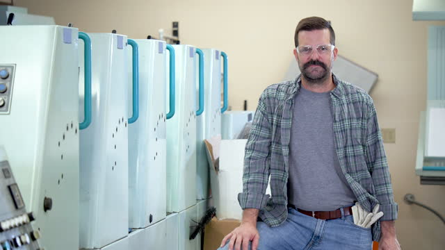 stockvideo's en b-roll-footage met rijpe mens die in drukinstallatie werkt - drukker