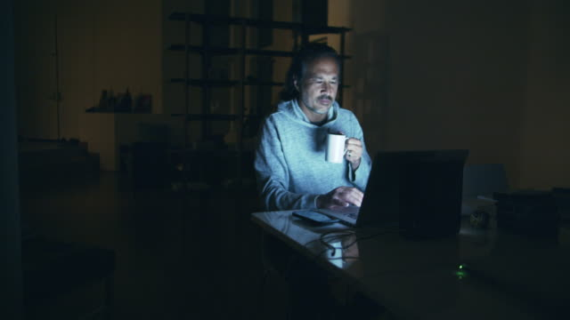 mature man working late at night at home - ensamhet bildbanksvideor och videomaterial från bakom kulisserna
