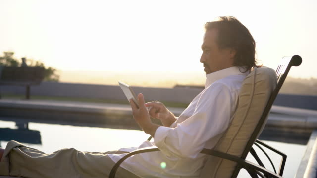 ms mature man working on a digital tablet by swimming pool at home - outdoor chair stock videos and b-roll footage