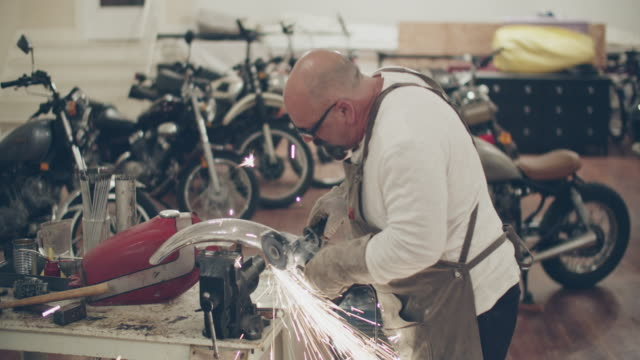mature man working on a motorcycle in a repair shop - completely bald stock videos & royalty-free footage