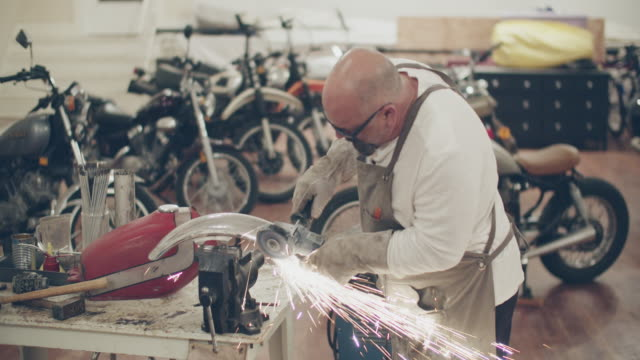 mature man working on a motorcycle in a repair shop - metalwork stock videos & royalty-free footage