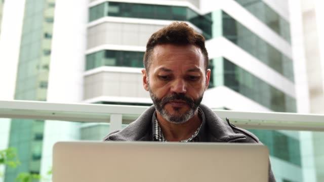 vídeos de stock, filmes e b-roll de homem maduro, trabalhando no laptop em casa - brasileiro pardo