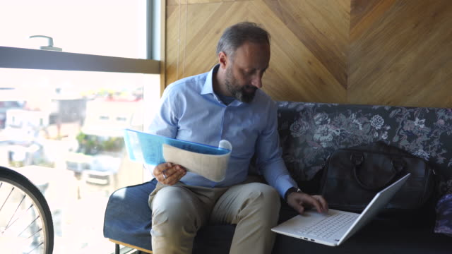 mature man writing on paper and using laptop - only mature men stock videos & royalty-free footage