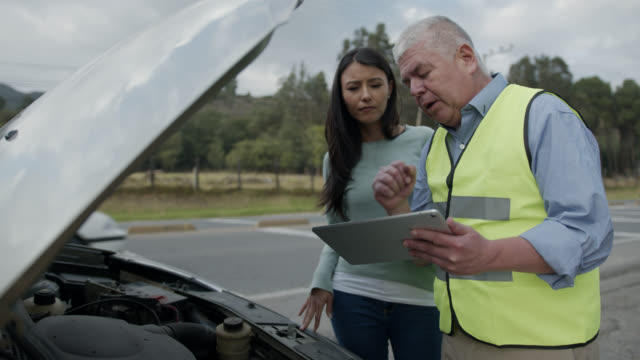 mature mechanic helping insurance female customer with a vehicle breakdown  holding a tablet - bonnet stock videos & royalty-free footage