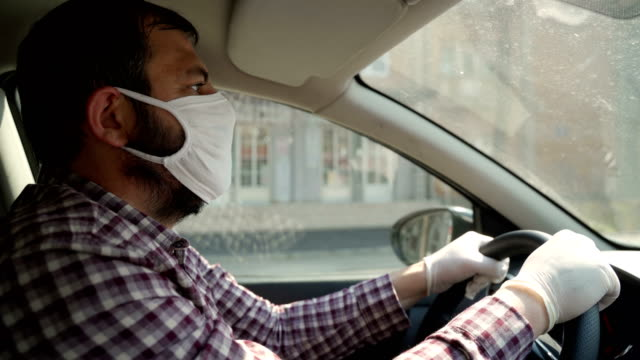 mature men driving a car with protective mask and protective gloves - driving stock videos & royalty-free footage