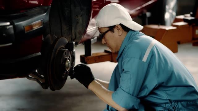 stockvideo's en b-roll-footage met volwassen mannen mechanisch onderzoeken auto schijf remblok slijtage van automotive voertuig - piercen