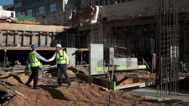 stockvideo's en b-roll-footage met mature men meeting on construction site - men