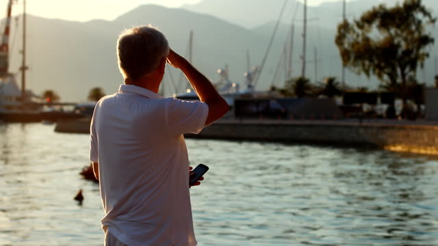 Mature men with smart phone in a Harbor