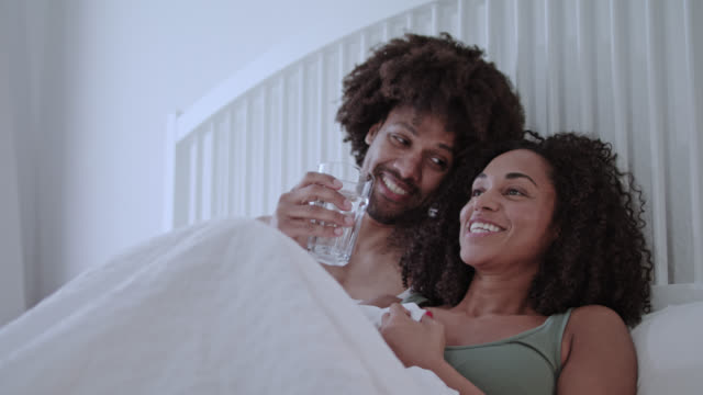 Mature mid adult dark-skinned mixed race married love couple at home happy staying in white bed on a weekend having a great time together while enjoying a glass of plain water.