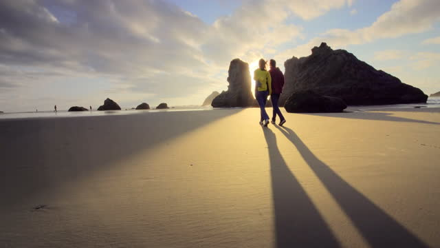 mature, middle aged couple strolling beach - oregon coast stock videos & royalty-free footage