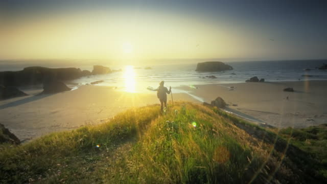 stockvideo's en b-roll-footage met mature middle aged woman hiking trail by ocean at sunset - footpath