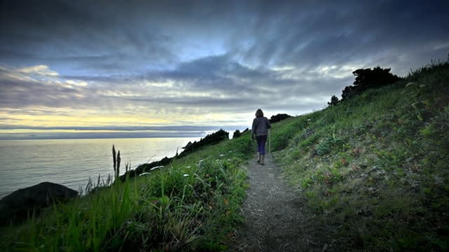 Mature middle aged woman hiking trail by ocean at sunset