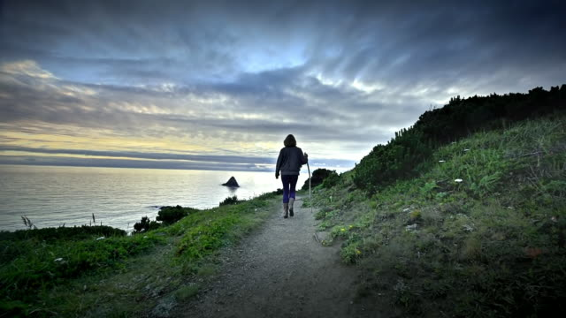 vidéos et rushes de mature middle aged woman hiking trail by ocean at sunset - suit