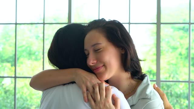 Reife Mutter und Erwachsene Tochter, die Zeit miteinander zu verbringen, in einem Heim umarmt fest.