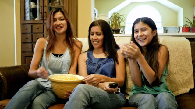 mature mother and teen daughters watching television and eating popcorn together - cable tv stock videos & royalty-free footage
