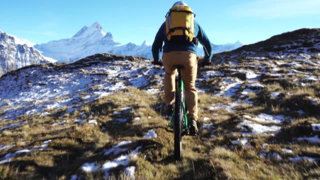 Mature mountain biker approaches summit on mountain bike