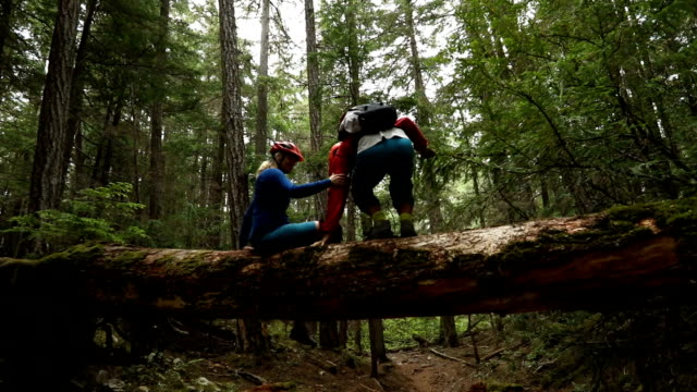 mature mountain biker couple balance on large log - mountain biking stock videos & royalty-free footage