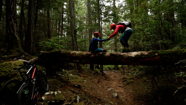 mature mountain biker couple balance on large log - trust stock videos & royalty-free footage