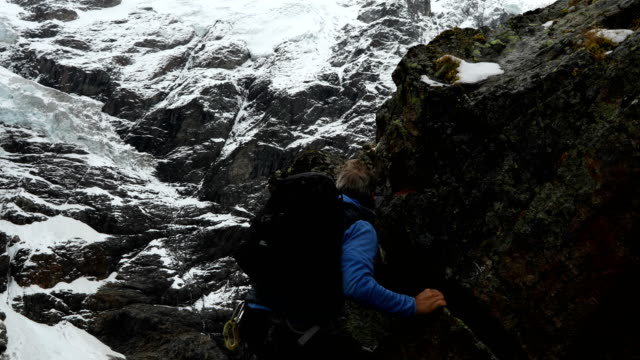 mature mountaineer ascends peak beneath a glaciated mountain face - only mature men stock videos & royalty-free footage