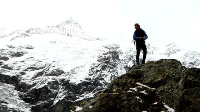 vídeos y material grabado en eventos de stock de mature mountaineer ascends peak beneath a glaciated mountain face - one mature man only