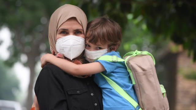 mature muslim woman carrying her son back to school, both wearing protective face masks child is carrying a backpack - illness stock videos & royalty-free footage