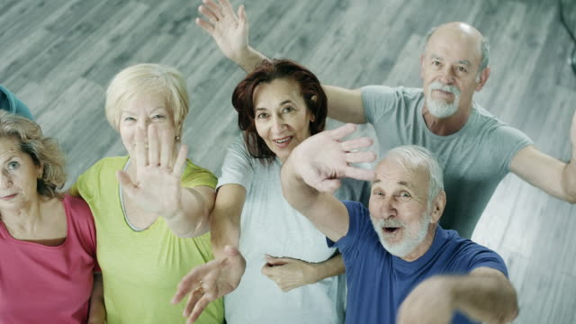 Mature People Waving Their Hands In The Gym