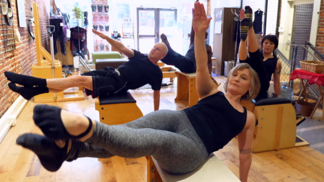ms mature pilates students exercising on pilates chair during class in fitness studio - pilates stock-videos und b-roll-filmmaterial