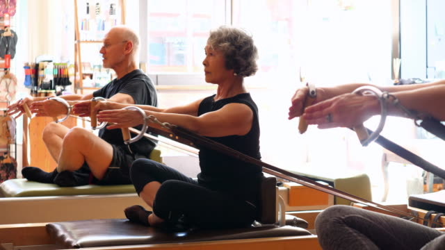 ms mature pilates students working out together during class in fitness studio - pilates stock videos & royalty-free footage