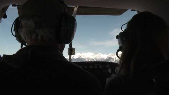 AERIAL WS SLO MO Mature pilot and passenger flying in small aircraft towards mountains / Missoula, Montana, USA